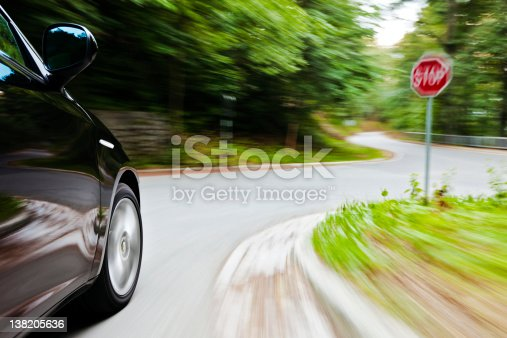 Motion blur of a car speeding towards the junction with Stop sign