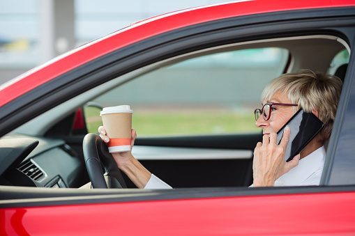 istock Reckless, smiling mature woman talking on the phone and holding a cup of coffee while driving a car 1055673422