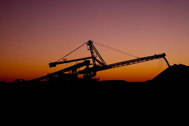 Reclaimer bei Sonnenuntergang auf Eisenerz Mine Site – Foto