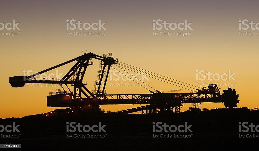 Reclaimer silhouette and iron ore stockpile royalty-free stock photo