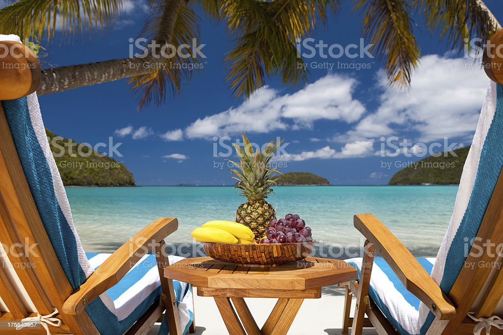 recliners and table with fruit at a Caribbean beach resort stock photo