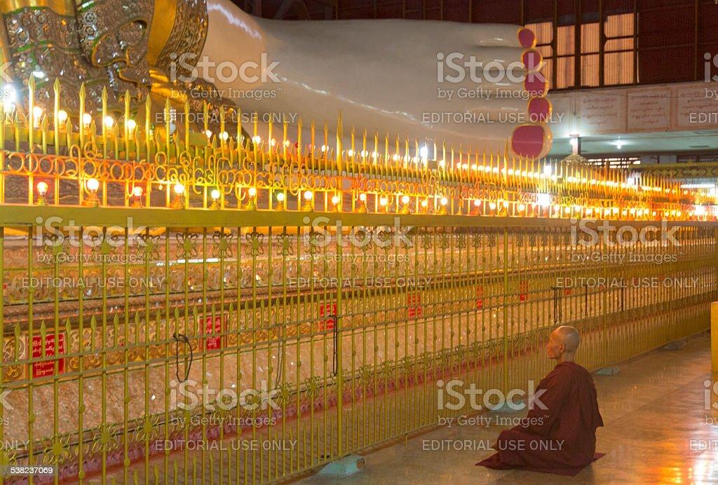 Reclining Buddha in Bago, Myanmar (Burma) with monk stock photo