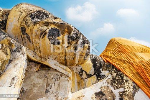 Reclining Buddha statue in festive safran clothes in Wat Lokaya Sutharam in Ayuttaya, Thailand. Lying Buddha statue