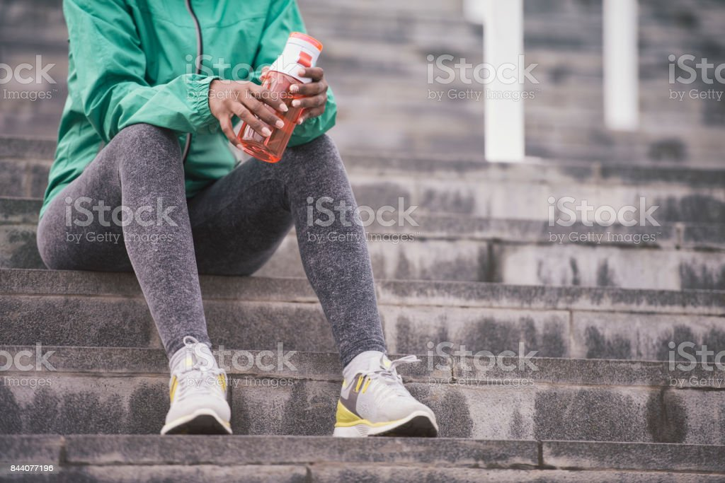 A recognizable athlete woman taking a break, drinking water. stock photo