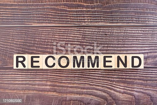 Recommend word made with building blocks on a wooden background