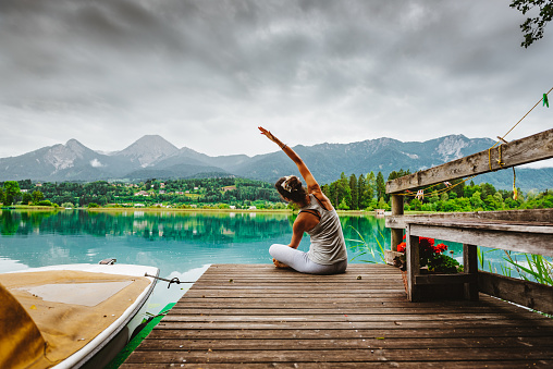 Reconnection to Nature – Outdoor Meditation and Yoga during sunrise on a jetty at Lake Faak, Austria, looking at mountain Mittagskogel/Kepa, the third highest mountain of the Karawanks mountain range