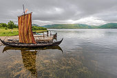 Reconstructed Viking ships in the border of Innerpollen salty lake in Vestvagoy island of Lofoten archipelago. The area is a part of Lofotr Historical museum. Nordland, Northern Norway.