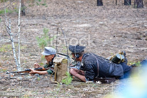 Ukraine, Voronezh - September 2, 2018: Reconstruction of the Second World War, german soldier communicates by radio in the forest.
