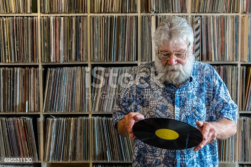 Record collector in front of his collection, looking at a vinyl record