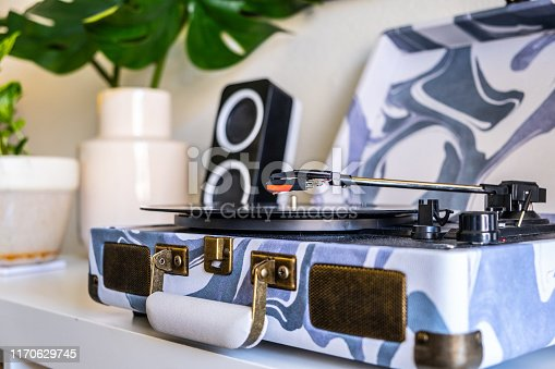 A record player sits on a white shelf in a small one bedroom studio apartment. The needle is hovering above the record about to touch down onto the surface of the vinyl.