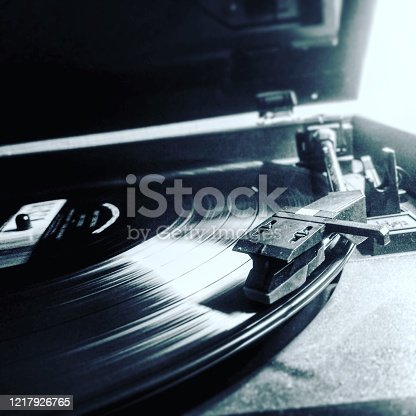 A black and white close up picture of a record player playing a record