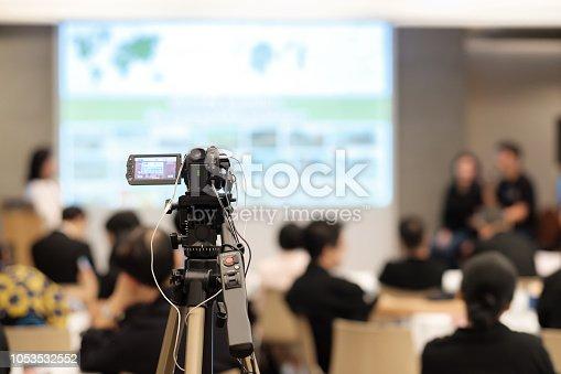 Video camera recording in seminar room.