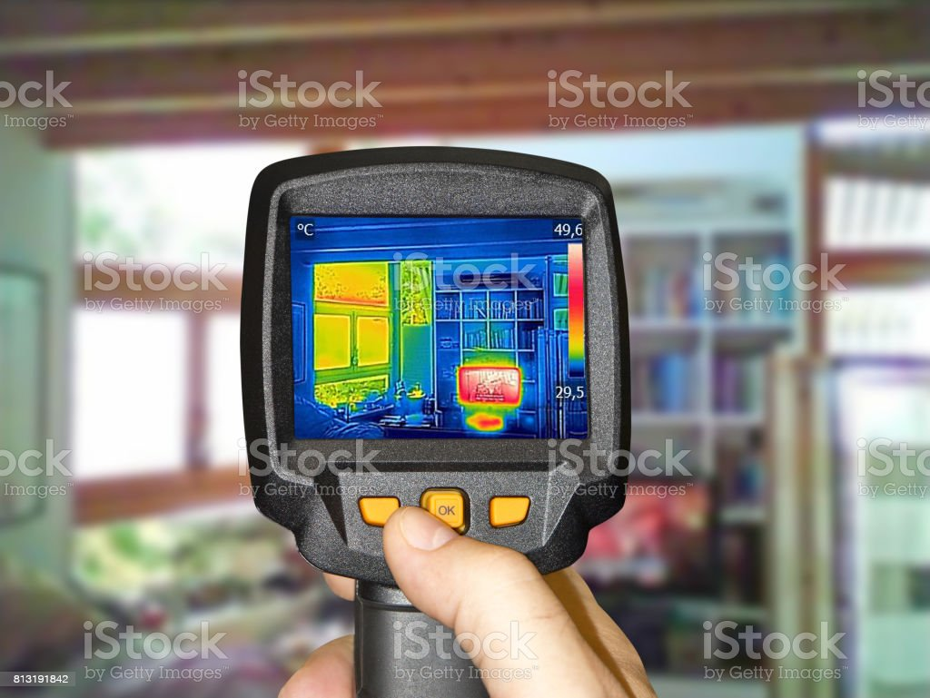 Recording heated TV and a window in the living room with thermal camera stock photo
