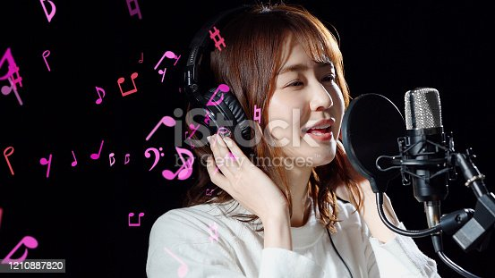 478117515 istock photo Recording of song concept. Young female asian singer. 1210887820