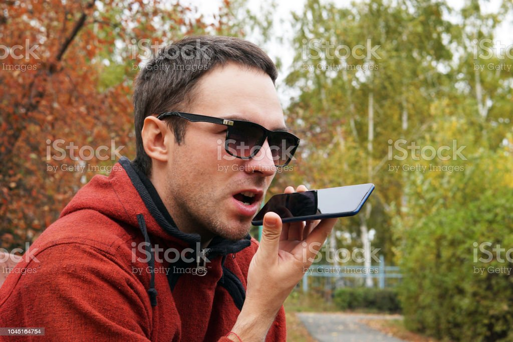 Recording on dictaphone. leisure, technology, communication and people concept - hipster man using voice command recorder or calling on smartphone at autumn park. dictate the thoughts in entry. stock photo