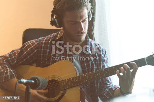 Casual guy playing guitar at home and recording it. He is listening it over headphones.