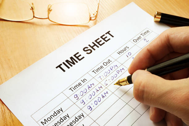 Records work hours in a time sheet. stock photo