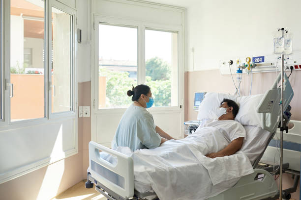 Recovering COVID-19 Patient and Visitor in Hospital Room stock photo