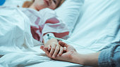 istock Recovering Little Child Lying in the Hospital Bed Sleeping, Her Hand Falls into Mother's and She Holds it Comfortingly. Focus on the Hands. Emotional Family Moment. 1038799992