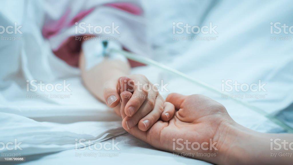 Recuperación niño pequeño acostado en la cama del Hospital para dormir, la madre sostiene su mano reconfortante. Se centran en las manos. Emotivo momento familiar. - foto de stock