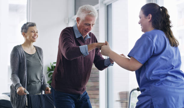 Recovery is easier with the right support Shot of a senior man in a wheelchair standing up with the help of a nurse fragility stock pictures, royalty-free photos & images
