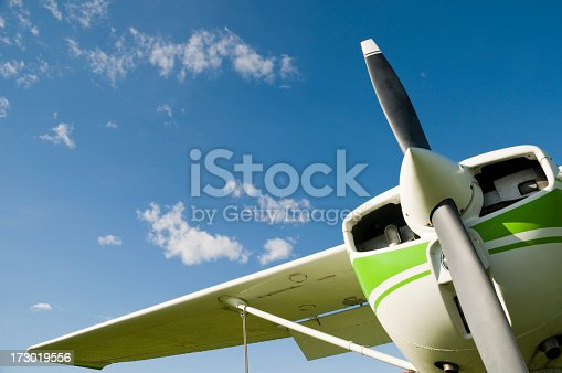 Front of a small airplane on a blue sky.