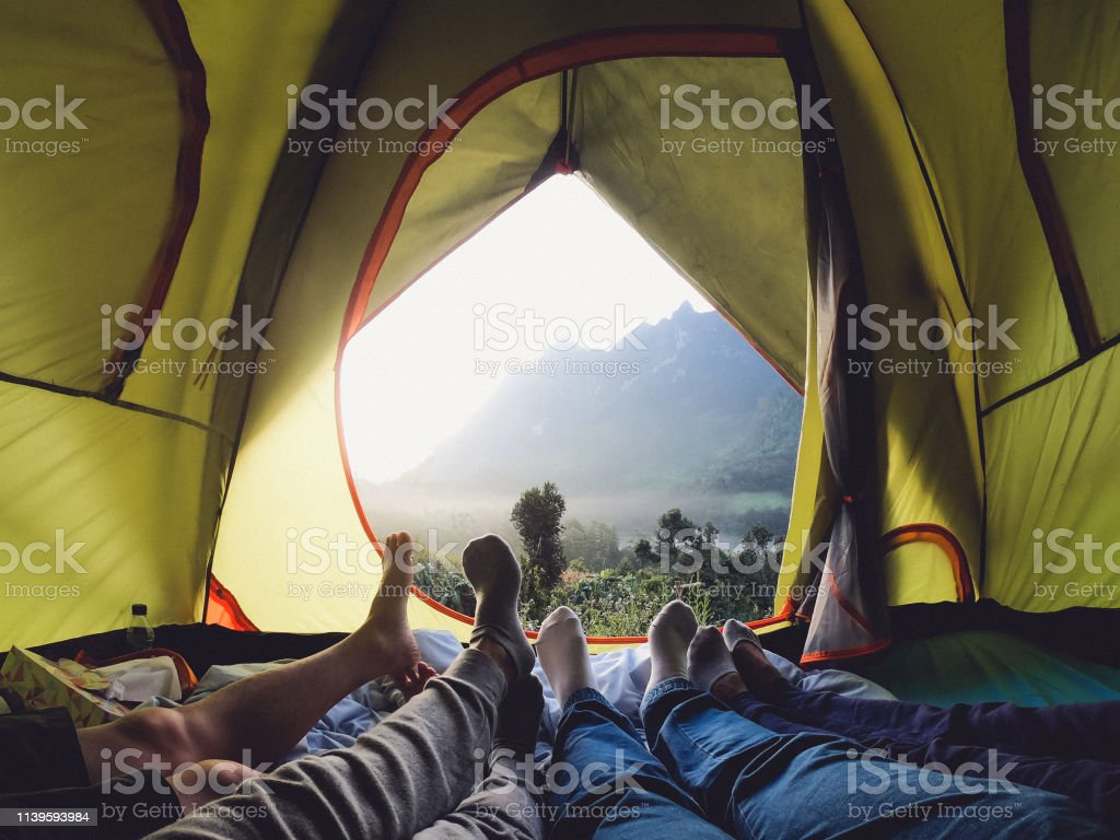 recreation at mountain in camping tent.group of feet lying down...