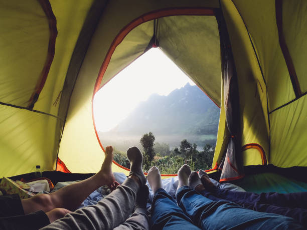 recreation at mountain in camping tent.group of feet lying down inside tent with mountain view in sunset with friend. stock photo