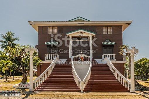 Puerto Princesa, Palawan, Philippines - March 3, 2019: Iwahig Penal Colony. Closeup of brown and white iconic Recreation Hall with broad staircase under blue sky. Green foliage.