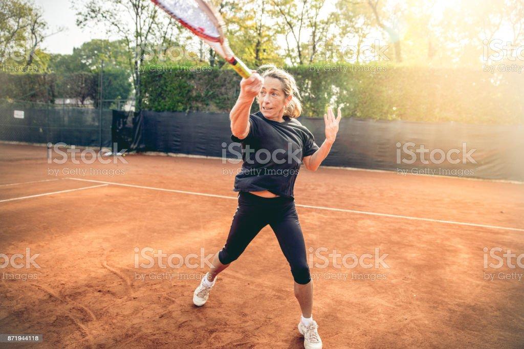 Recreational Adult Female Swinging a Racket stock photo