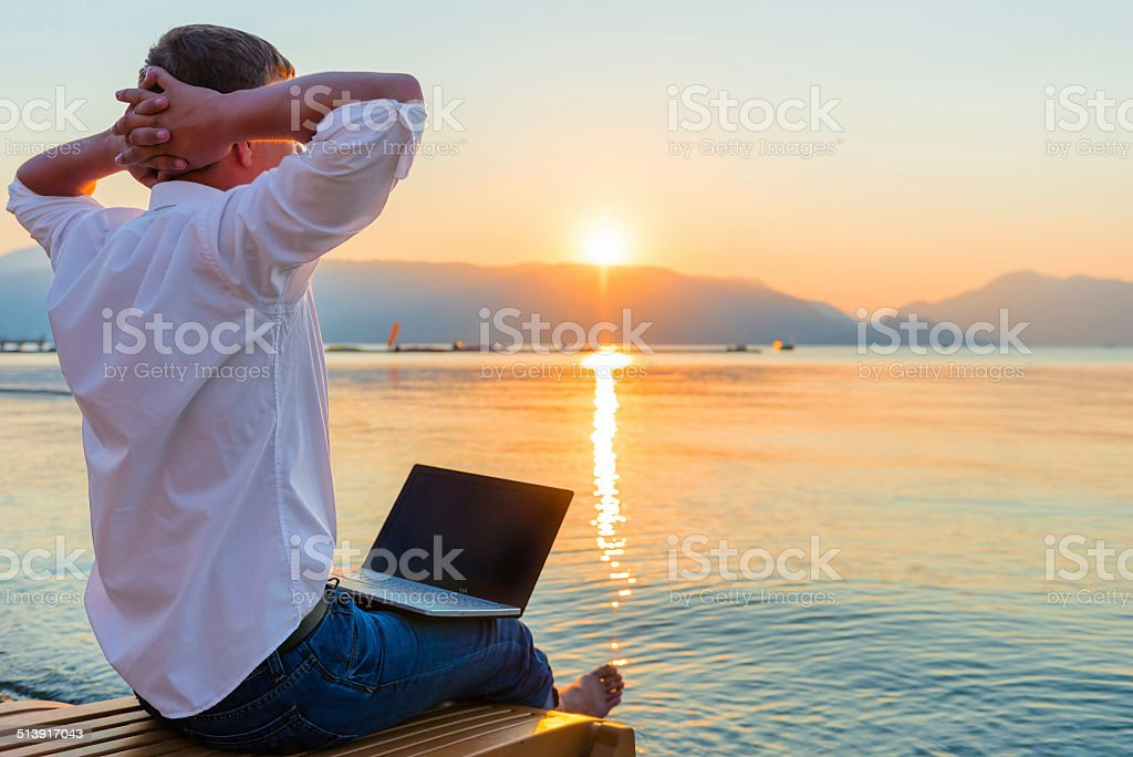 Recreational entrepreneur. Man with laptop in the morning on the stock photo