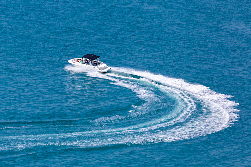 Recreational high speed motorboat makes sudden turn at sea