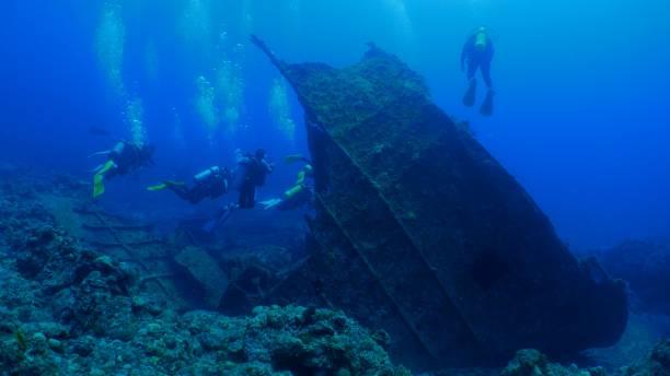 Recreational scuba divers in underwater wreck stock photo
