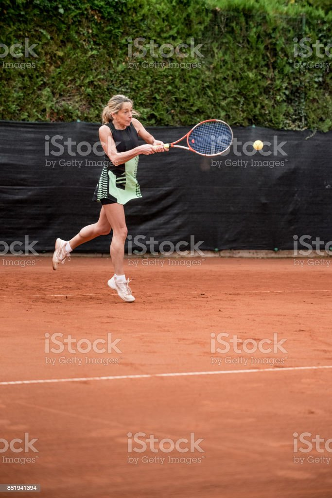 Recreational Tennis Player After Hitting the Ball stock photo