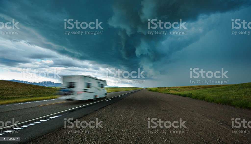 Recreational Vehicle Camper Driving on Highway Under Dark Storm Clouds stock photo