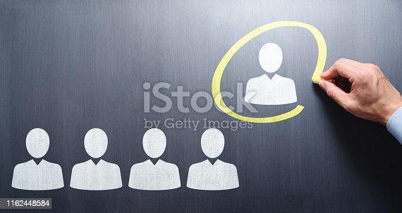 Selecting person. Manager drawing businesspeople icons and circle on chalkboard.