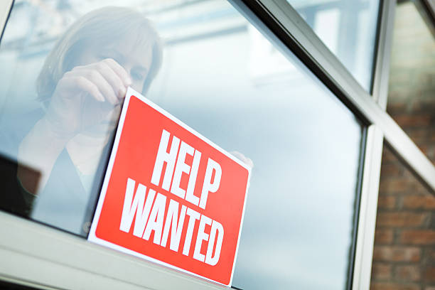 """HELP WANTED Recruitment Sign Displayed for Hiring, Employment, Economic Recovery Sign of hiring, recruitment, employment and economic recovery through a woman business person posting a """"HELP WANTED"""" sign for new employees. help wanted sign stock pictures, royalty-free photos & images"""