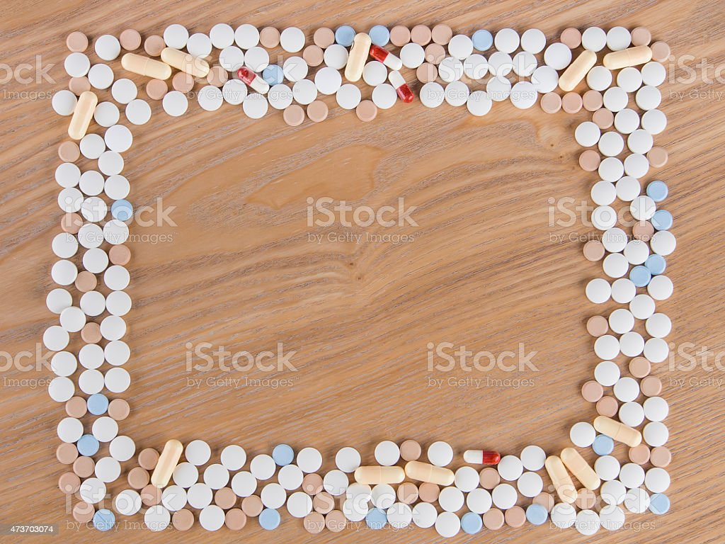 Tablets and capsule arranged into rectangle frame on a wooden...