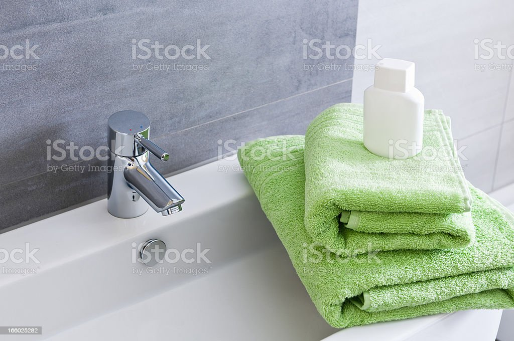 Rectangular bathroom sink with one green and one orange towel stock photo