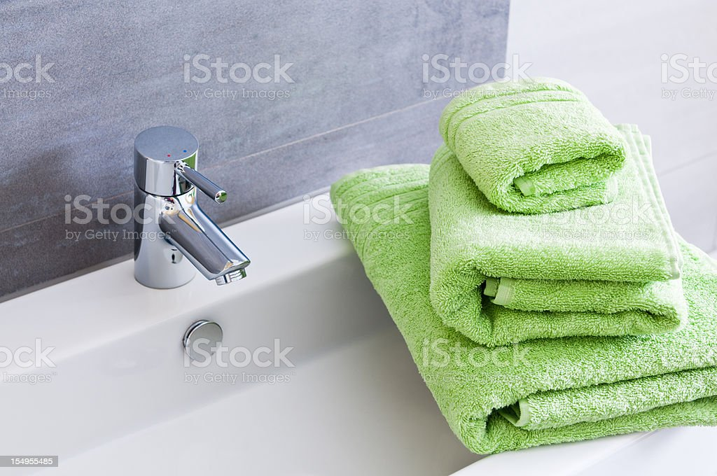 Rectangular bathroom sink with tap and three green towels stock photo