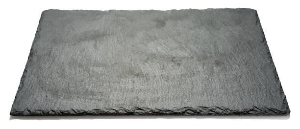 rechteckige schwarz strukturiert schiefer board für gerichte, die isoliert auf weißem hintergrund, winkel seitenansicht mit perspektive - winkel stock-fotos und bilder