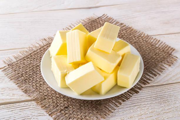 rectangular pieces of fresh yellow butter on a white saucer over a white wooden table. dairy. sandwich butter. natural fat nutrient. - manteiga imagens e fotografias de stock