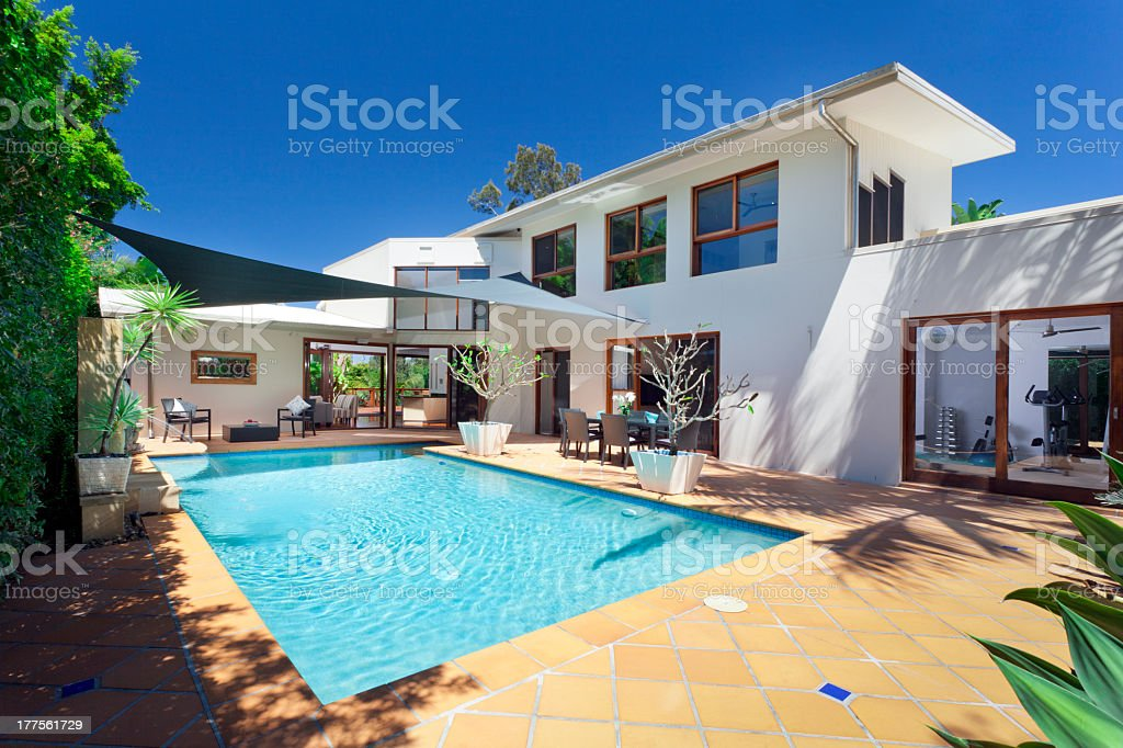 Rectangular swimming pool in back of a large white house stock photo