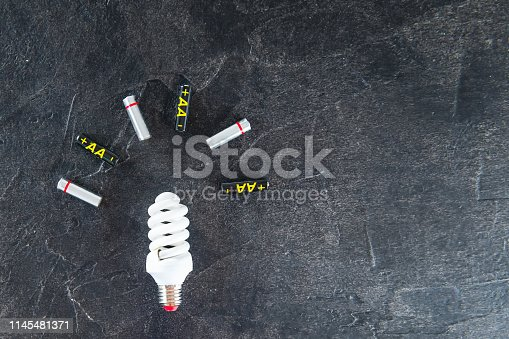 istock Recycle, alternative energy concept with led lamp and batteries. Hazardous waste on a black stone background with space for text. 1145481371