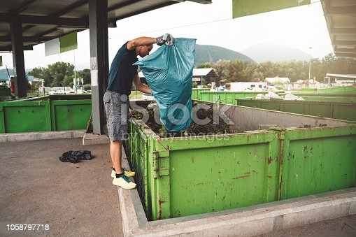 Happy man is taking care of the environment by recycling waste at the recycle facility near his home. Wearing protective gloves, he is dumping a bag full of organic waste into organic waste container.