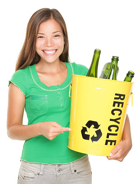 Recycle girl Recycle! Recycling woman pointing at recycle icon on bin with glass bottles. Caucasian / Asian girl isolated on white background. See more bottle bank stock pictures, royalty-free photos & images