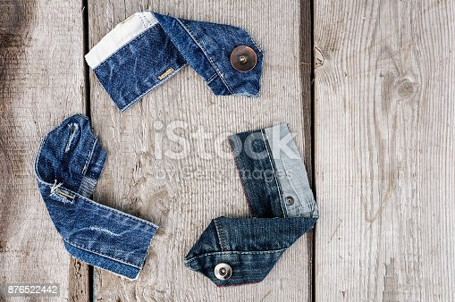 Recycle Logo from used old denim fabric on old grey wooden background — Photo by HappyCity