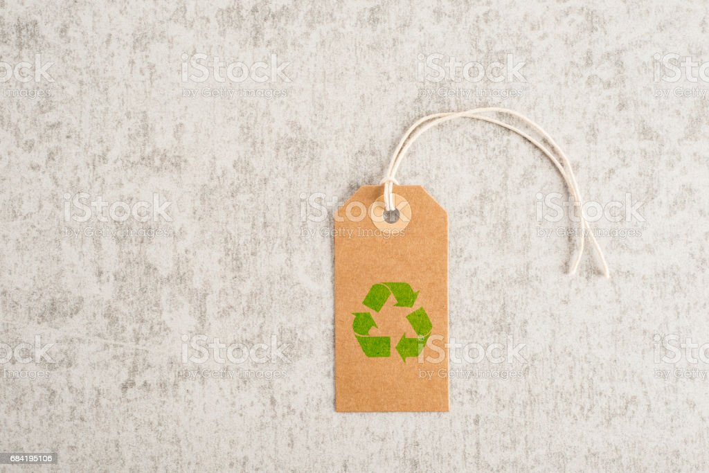 Recycle symbol on brown paper tag royalty-free stock photo
