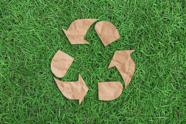 recycle symbol on green grass background top view. eco and save the earth concept. - riciclaggio foto e immagini stock