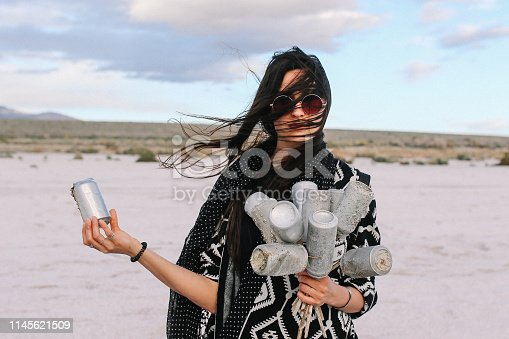Young woman collecting the thrash cans by the Salton Sea - lake in Southern California, near Coachella Valley. Nature preservation, recycling concepts, presented by a modern, hippie-boho young woman.